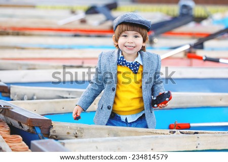Cheerful happy boy with trendy autumn or spring outfit standing in boat at harbor. Smiling toddler with fancy jacket, hat and tie bow.  - stock photo