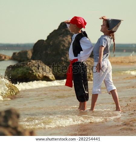 Cheerful happy cute boy and girl in pirate costumes barefoot run along the sea coast