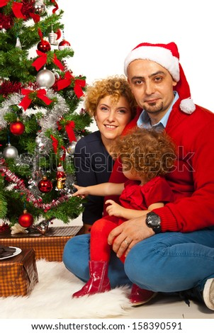 Cheerful happy family standing near Christmas tree