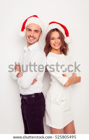 Cheerful happy man and woman in red santa hats standing back to back.