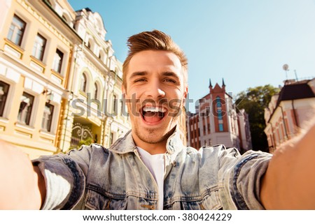 Cheerful happy man making selfie photo on the street - stock photo