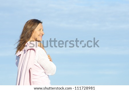 Cheerful, happy smiling attractive senior woman enjoying retirement, isolated, with blue sky as background and copy space. - stock photo