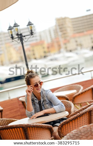 Cheerful happy smiling pretty female in restaurant on luxury marina background. enjoying travel life concept - stock photo