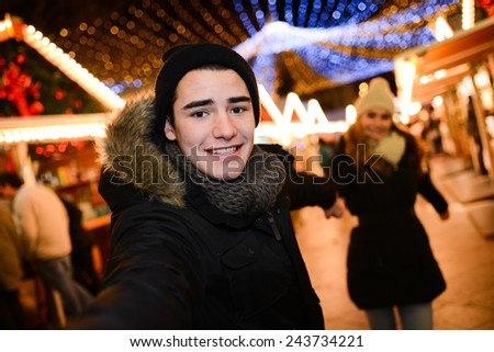 cheerful happy young couple having fun downtown at night during winter  - stock photo