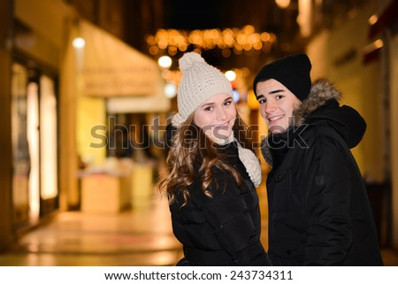 cheerful happy young couple having fun downtown at night during winter