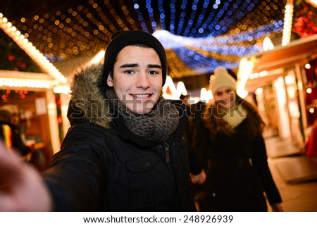 cheerful happy young couple having fun downtown at night during winter time  - stock photo