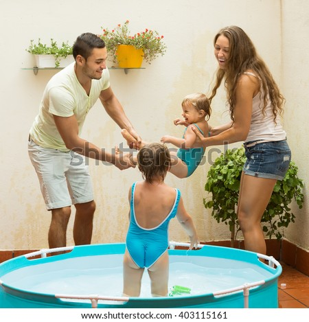 Cheerful happy young family of four playing in pool at terrace - stock photo