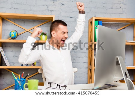 Cheerful happy young  man triumphing with raised hands - stock photo