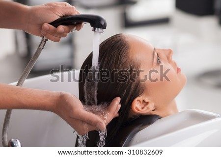 Cheerful healthy girl is getting a hairwash in hair salon. She is sitting and leaning her head on the sink. The lady is relaxing and looking forward with happiness. The beautician is holding a faucet  - stock photo