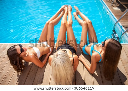 Cheerful healthy girls are getting a suntan on vacation. They are lying on flooring near a swimming pool. The lady are raising their legs and smiling - stock photo