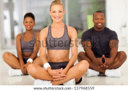 cheerful healthy woman relaxing after exercise with two friends - stock photo