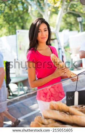 cheerful healthy young woman shopping in farmers market and buying fresh bio artisan bread - stock photo