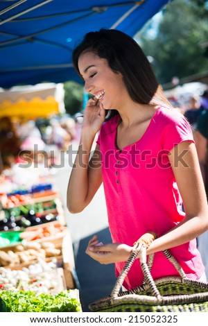 cheerful healthy young woman shopping in farmers market buying nice fresh organics fruits and vegetables - stock photo