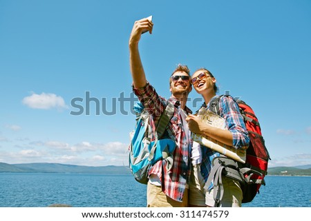 Cheerful hikers making selfie during trip against blue sky - stock photo