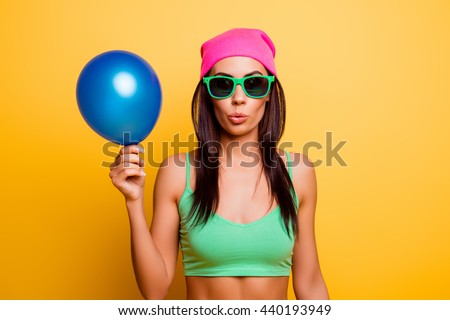 Cheerful hipster girl in pink hat  holding balloon on yellow wall - stock photo