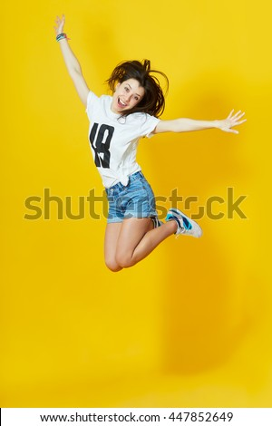 Cheerful hipster girl jumpig with hands spread wide over yellow background. Young woman in jump. - stock photo