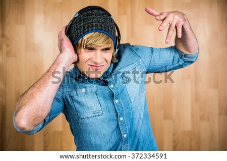Cheerful hipster listening to music with hands on ears - stock photo