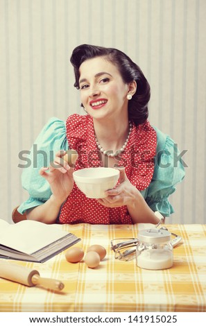 Cheerful housewife cooking in the kitchen - stock photo