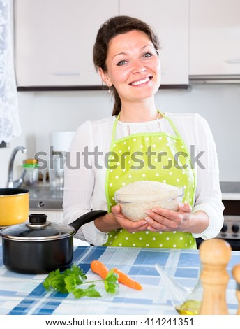Cheerful housewife in green apron cooking rice in a pan in kitchen - stock photo