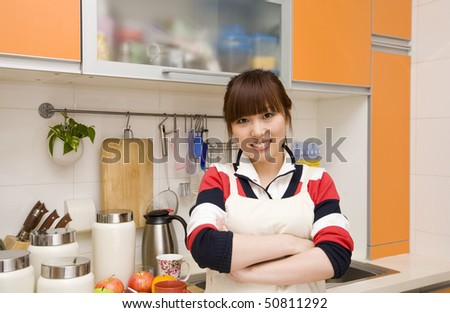 cheerful housewife in her kitchen - stock photo