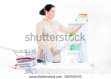 Cheerful housewife standing at the ironing board ironing clothes - stock photo