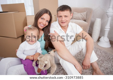 Cheerful husband and wife are moving in another building. They are embracing and smiling. The couple is sitting on flooring ahead the cardboard boxes. The woman is holding her little daughter - stock photo