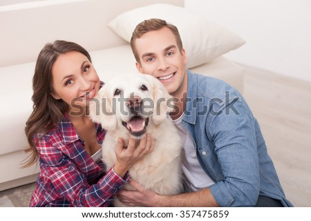 Cheerful husband and wife are playing with a dog on the floor. They are sitting and stroking a puppy with love. The man and woman are smiling - stock photo