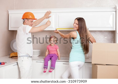 Cheerful husband and wife with little child are preparing to move in new house. They standing in kitchen and smiling. A woman is measuring furniture. The men is working with screwdriver - stock photo
