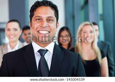 cheerful indian businessman with colleagues on background - stock photo