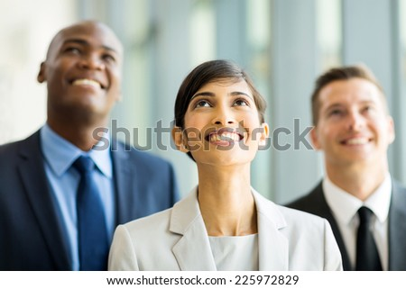 cheerful indian businesswoman and team looking up - stock photo