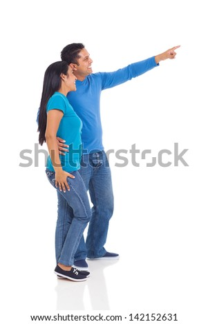 cheerful indian couple pointing at empty copy space on white background - stock photo