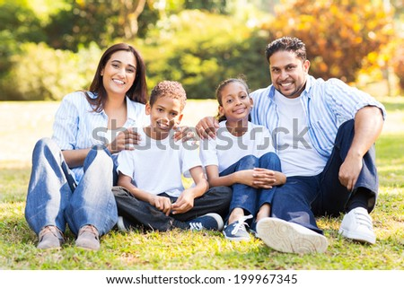 cheerful indian family sitting together outdoors - stock photo