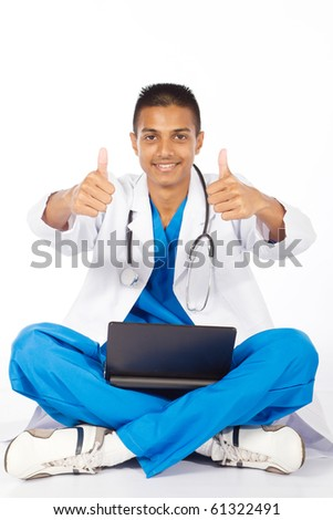 cheerful indian medical intern giving thumbs up - stock photo