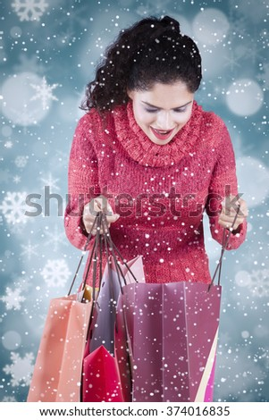 Cheerful indian woman opens shopping bags while wearing winter clothes with winter background - stock photo