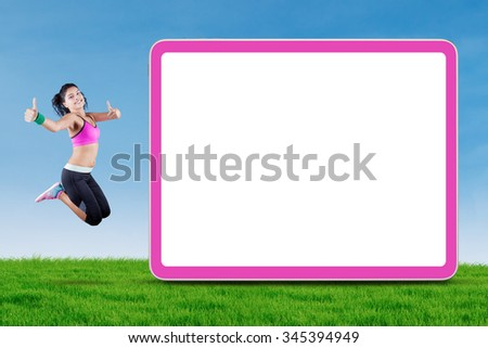Cheerful indian woman wearing sportswear and jumping at field near the empty billboard while showing thumbs up - stock photo