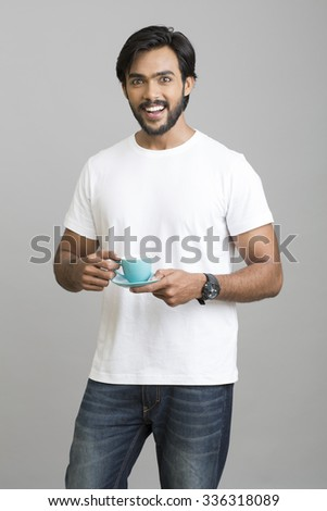 Cheerful Indian young man with coffee cup on grey background. - stock photo