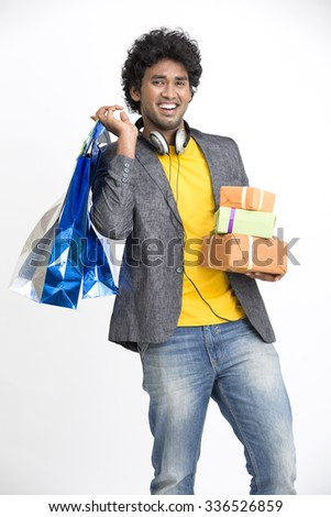 Cheerful Indian young man with shopping bags and gift boxes - stock photo