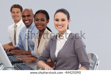 Cheerful international business partners sitting in a line in the office