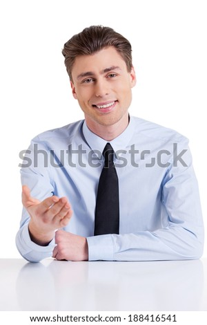 Cheerful interviewer. Handsome young man in shirt and tie sitting at the table and gesturing while isolated on white   - stock photo