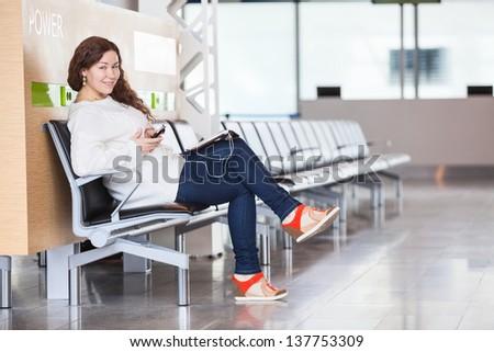 Cheerful joyful Caucasian woman spending time in airport lounge - stock photo