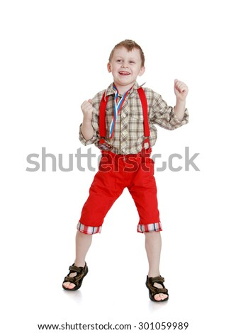 Cheerful, joyful little boy in a plaid shirt and long red shorts. Boy waving fists with joy.-Isolated on white background - stock photo