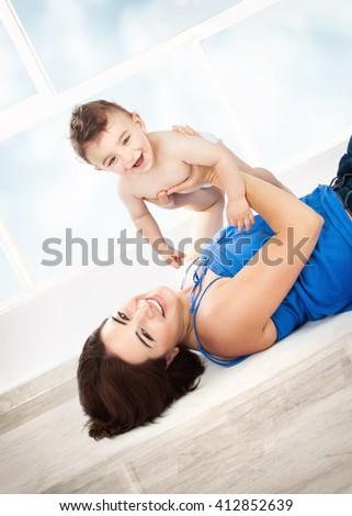 Cheerful joyful mother playing with her adorable son, lying down on the floor at home, enjoying motherhood, happy family life - stock photo