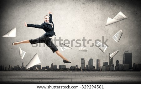 Cheerful jumping businesswoman and papers flying in air