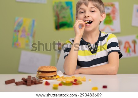 Cheerful kid at school eating unhealthy snacks - stock photo