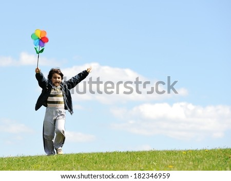 Cheerful kid having fun running on green summer meadow - stock photo