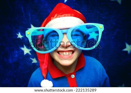 Cheerful Kid in Big Glasses and Santa's Hat - stock photo