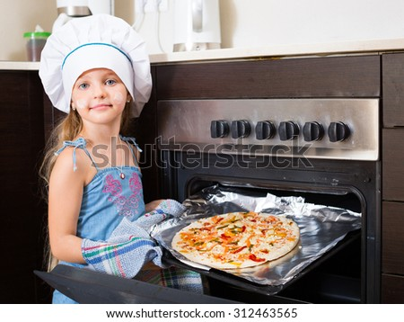 Cheerful kid prepared Italian pizza at home - stock photo