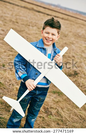Cheerful kid with toy airplane looking at camera outside - stock photo