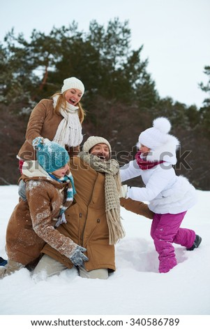 Cheerful kids and parents having fun in snowdrift - stock photo