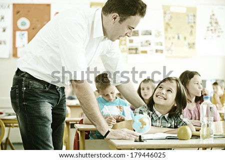Cheerful kids at school room having education activity helped by teacher - stock photo